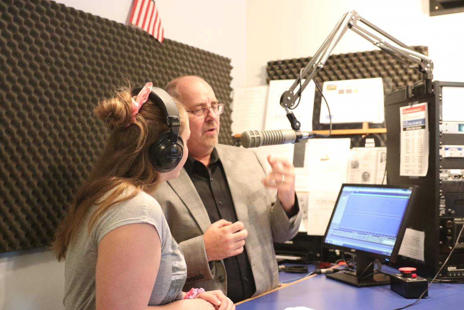 2.%09Voices+of+Montana+radio+host+Tom+Schultz+demonstrates+proper+microphone+use+to+student+Desiree+Swanson+in+the+Northern+News+Network+station.